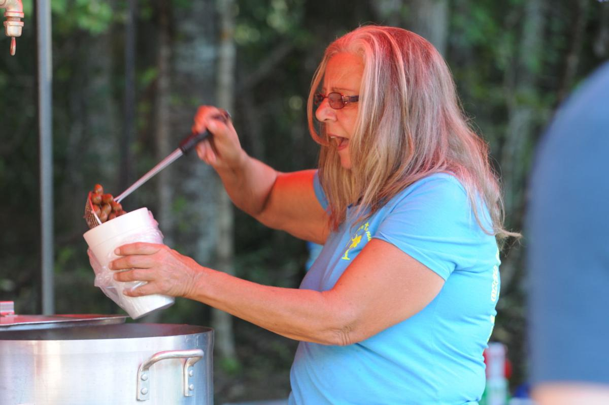 Debbie Keley pours a festivalgoer a cup of Uncle Chuck's Boiled Peanuts. By Roger Lee