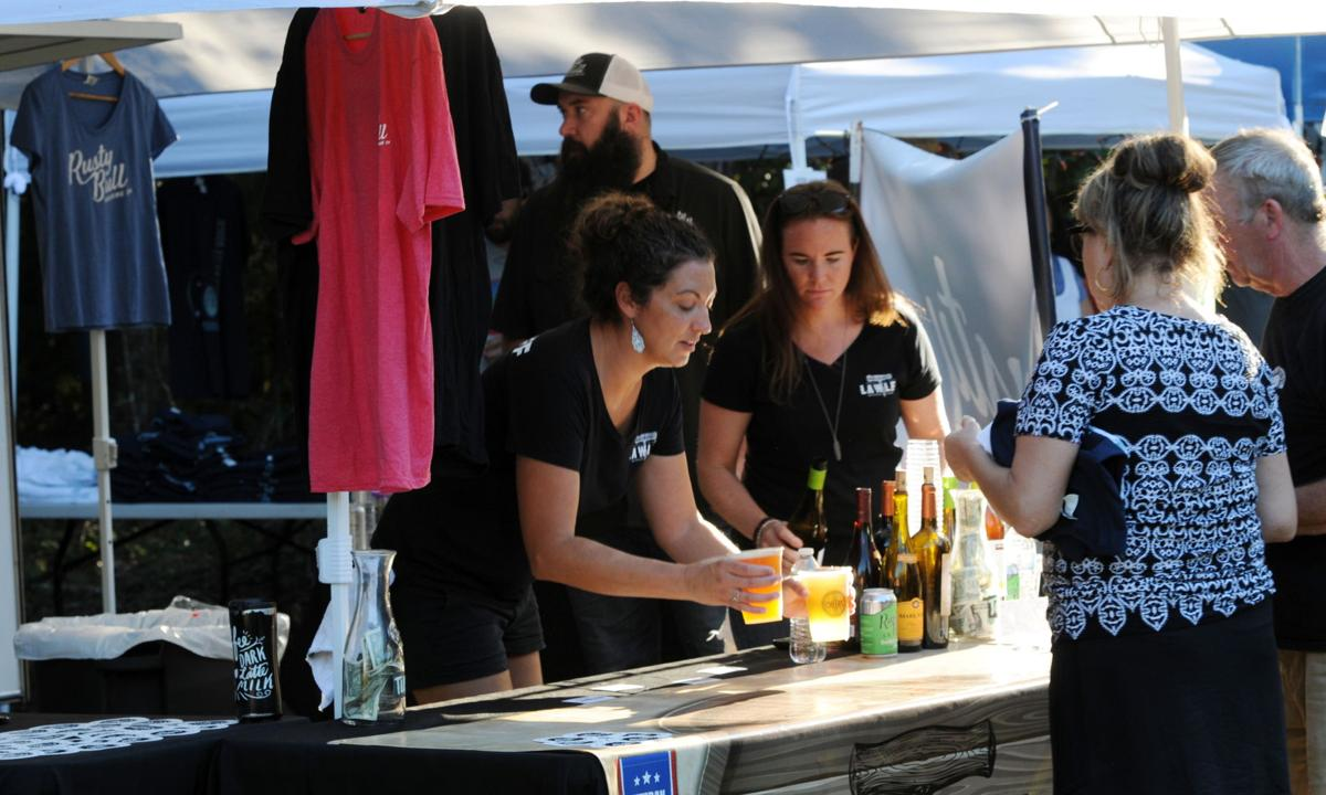 Sarah Elzinga serves up a couple of beverages at the Lawler Beverage Company booth. By Roger Lee
